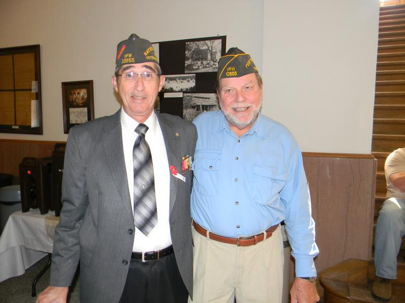 Two men one in blue and one in a suit, both in Vietnam Veteran hats, side hug each other and smile at the camera